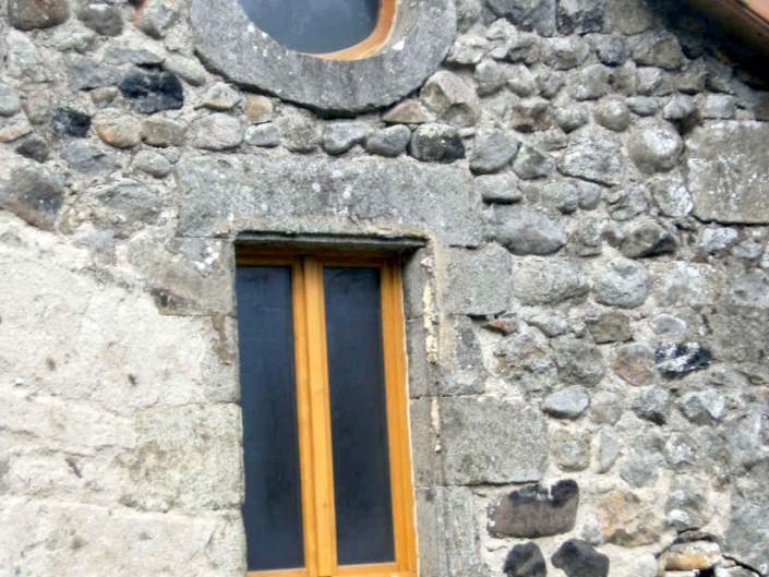 Fenêtre bois accompagnée d'un œil de bœuf en bois